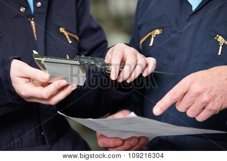 Close Up Of Engineers Measuring Component With Micrometer