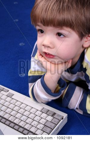 Young Boy Working On A Laptop