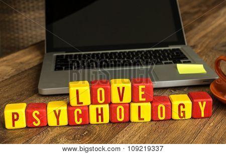 Love Psychology written on a wooden cube in a office desk