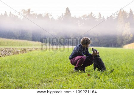 Young Man Crouching To Pet His Black Dog In A Beautiful Green Meadow