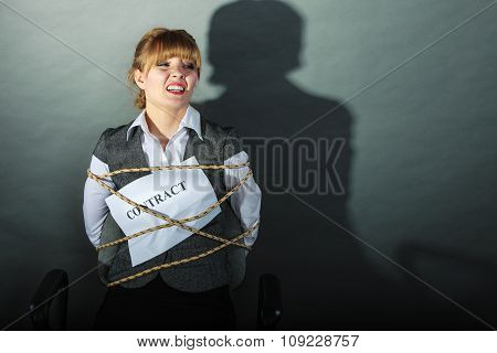 Afraid businesswoman bound by contract terms and conditions. Terrified scared woman tied to chair become slave. Business and law concept. poster
