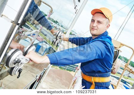 Worker builder installing windows with glass suction plates on facade of business building