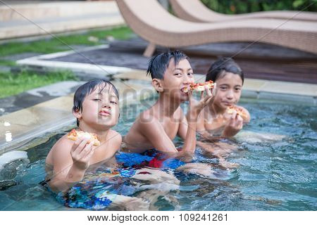 Three Boys Enjoying The Pool While Eating A Bread