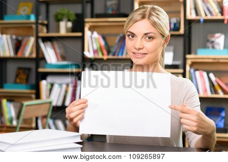 Young girl is holding a sheet of paper.