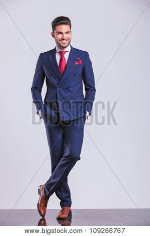 young man in suit posing with legs crossed while having hands in pockets