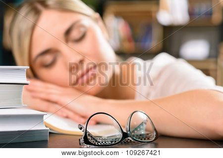 Young girl is asleep on the desk.