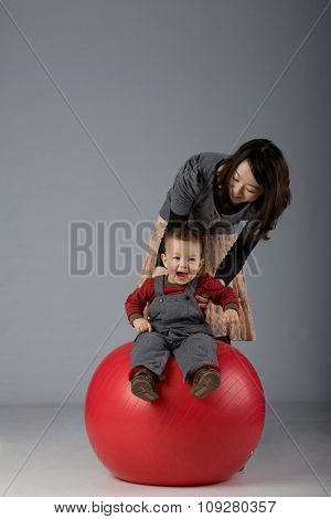 portrait of a japanese mother and toddler son playing on a fit pall
