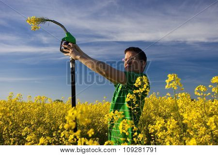Eco fuel concept: young man in nature with gas station nozzle with flowers