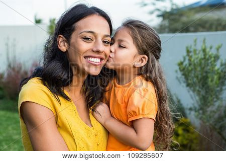 Cute daughter kissing her mothers cheek outdoors