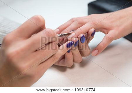Manicurist removing cuticle with metal pusher