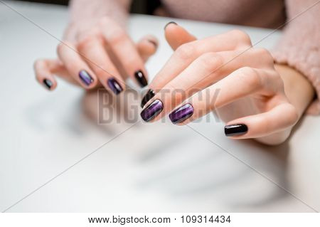 Finished shellac manicure client girl in nail beauty salon. Hands lie on white table and show the beautiful manicure. poster