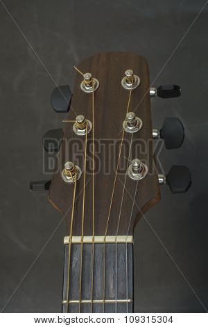 Headstock,fret bord, frets, tuners of guitar acoustic.