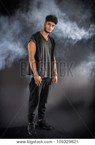 Tough young man in dark t-shirt on grey background