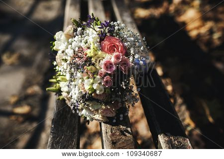 beautiful bridal bouquet lying on a bench