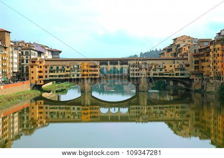Pone Vecchio over Arno river with its reflection in Florence Italy