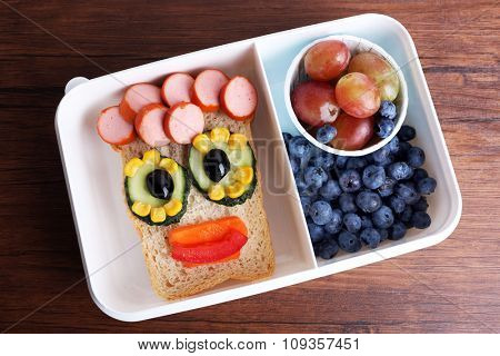 Creative sandwich with fruits in lunchbox on wooden background