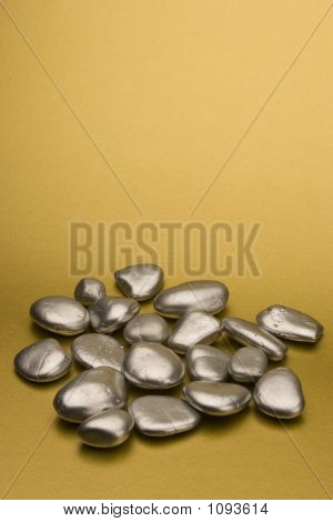 silver painted stones set against a gold background. poster