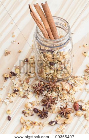 Pile of granola cereal and cinnamon sticks on the wood background poster