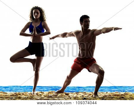 one caucasian couple man and woman yoga exercices on the beach silhouette isolated on white background