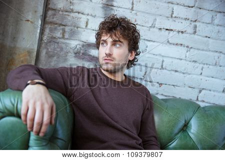 Pensive attractive thoughtful curly young man in brown sweetshirt thinking on green leather sofa alone