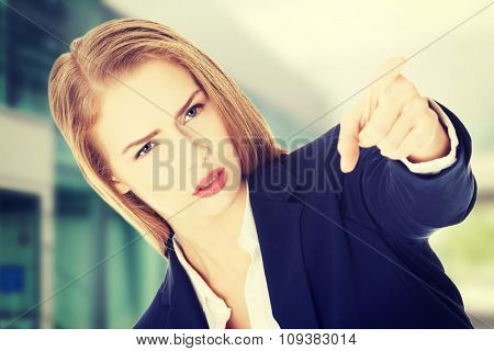 Beautiful business woman is showing warning sign