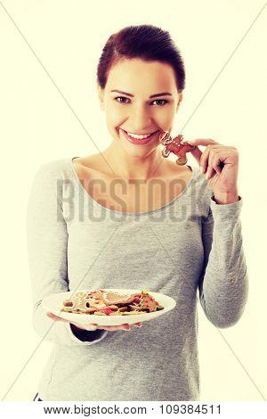 Happy woman eating christmas cookies.