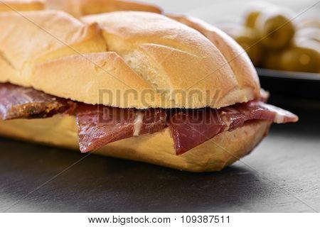 closeup of a spanish bocadillo de jamon serrano, a serrano ham sandwich, on a slate stone background