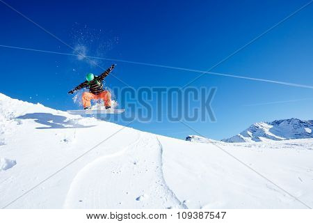 Male snowboarder wearing green helmet, black jacket and orange pants having fun jumping against blue sky on ski resort piste - winter sports concept