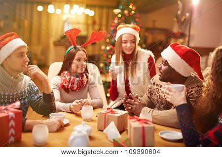 Friendly guys and girls talking while having tea on Christmas evening