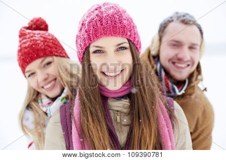 Happy friends in winterwear looking at camera during snowfall