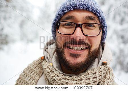 Happy Asian guy in winterwear looking at camera outside