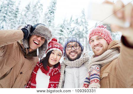 Happy friends in winterwear making selfie in park