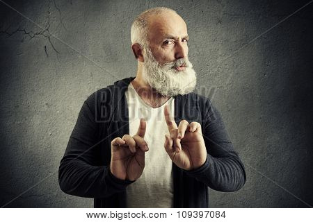 senior bearded man showing refusal sign and looking at camera over dark wall