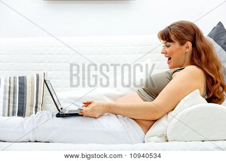 Pleased beautiful pregnant woman sitting on sofa with laptop and credit card