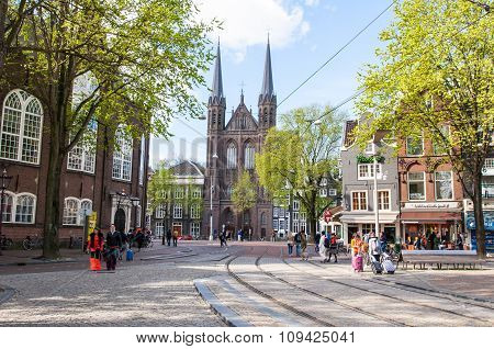 AMSTERDAMNETHERLANDS-APRIL 27: Krijtberg Kerk facade in the distance on King's Day on April 272015 in Amsterdam Netherlands. De Krijtberg Kerk is a Roman Catholic church at the Singel canal.