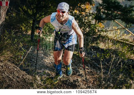 male athlete in forest is Hiking traill with nordic walking poles