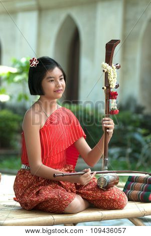 Thai Girl In Traditional Dress In Playing Thai Fiddle.