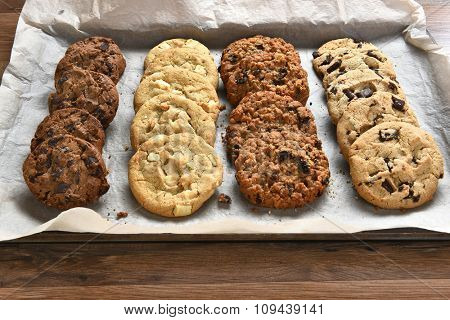 Closeup of a tray of fresh baked cookies, Chocolate Chip, oatmeal raisin Chocolate and white chocolate chip cookies on baking sheet and parchment paper.