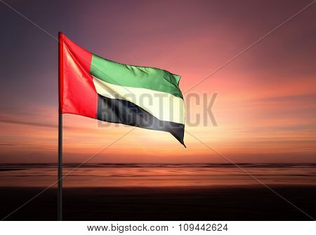 Flag of United Arab Emirates flying against beautiful morning sky. UAE celebrates national day on December 2.