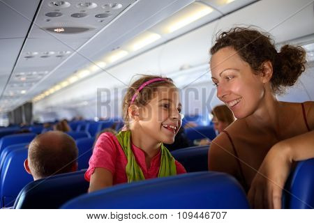 Mother and daughter smiling at each other on an airplane