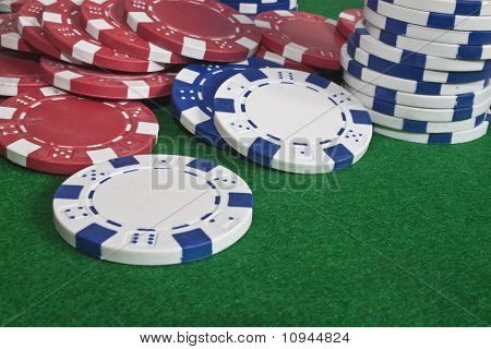 Scattered Poker Chips On A Green Beize