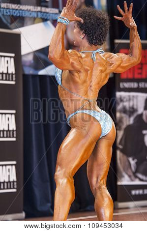 Female Bodybuilder In Back Double Biceps Pose And Blue Bikini