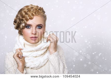 portrait of a beautiful young blonde woman on a light background. hair tied in a braid. girl wearing