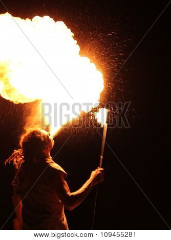Byron Beach, Australia - August, 2015: Man fire-eater blowing a large flame from his mouth ( man spi