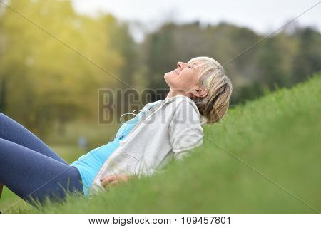 Senior woman in fitness outfit relaxing in park