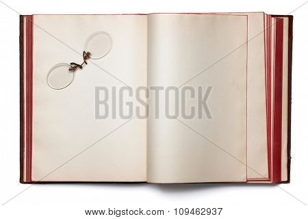 rimless glasses on a blank book spread