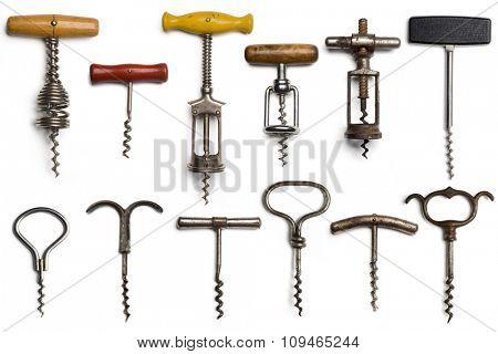 a collection of dozen vintage corkscrews on white