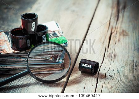 Photo Film Rolls, Stack Of Photos And Magnifier On Desk