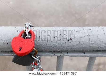 red lock in heart shape with drops of rain