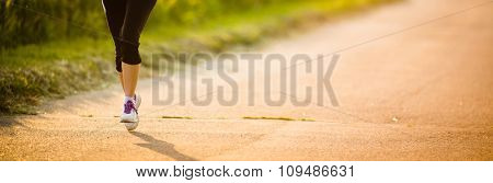 Detail of legs of a female runner on road - jog workout/well-being concept